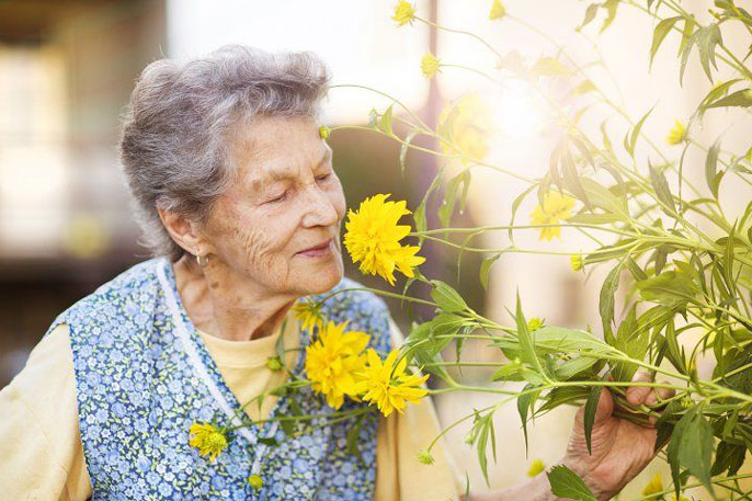 Older woman smelling flowers
